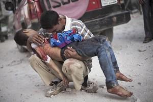 Tată care ține în brațe cadavrul fiului, ucis în urma unui bombardament în Alep, Siria (foto: www.sfgate.com)