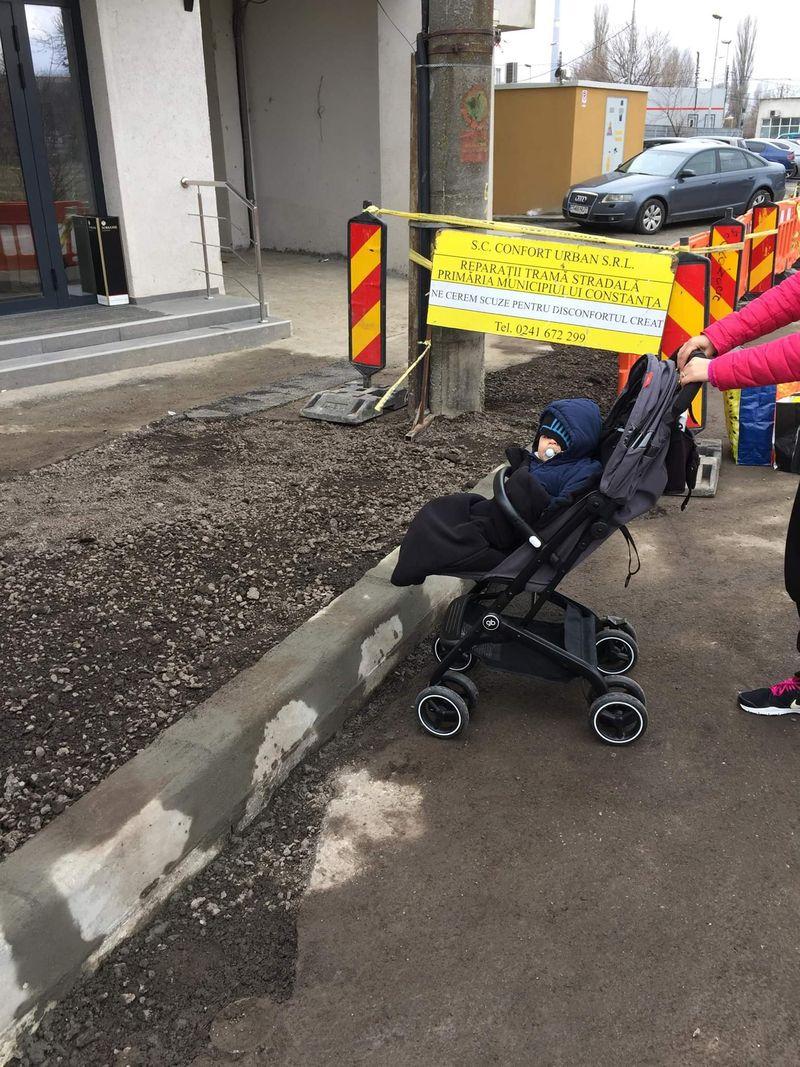 O mămică încearcă să urce un bebeluș aflat în cărucior peste bordura înaltă amplasată de Confort Urban chiar la intrarea în bloc