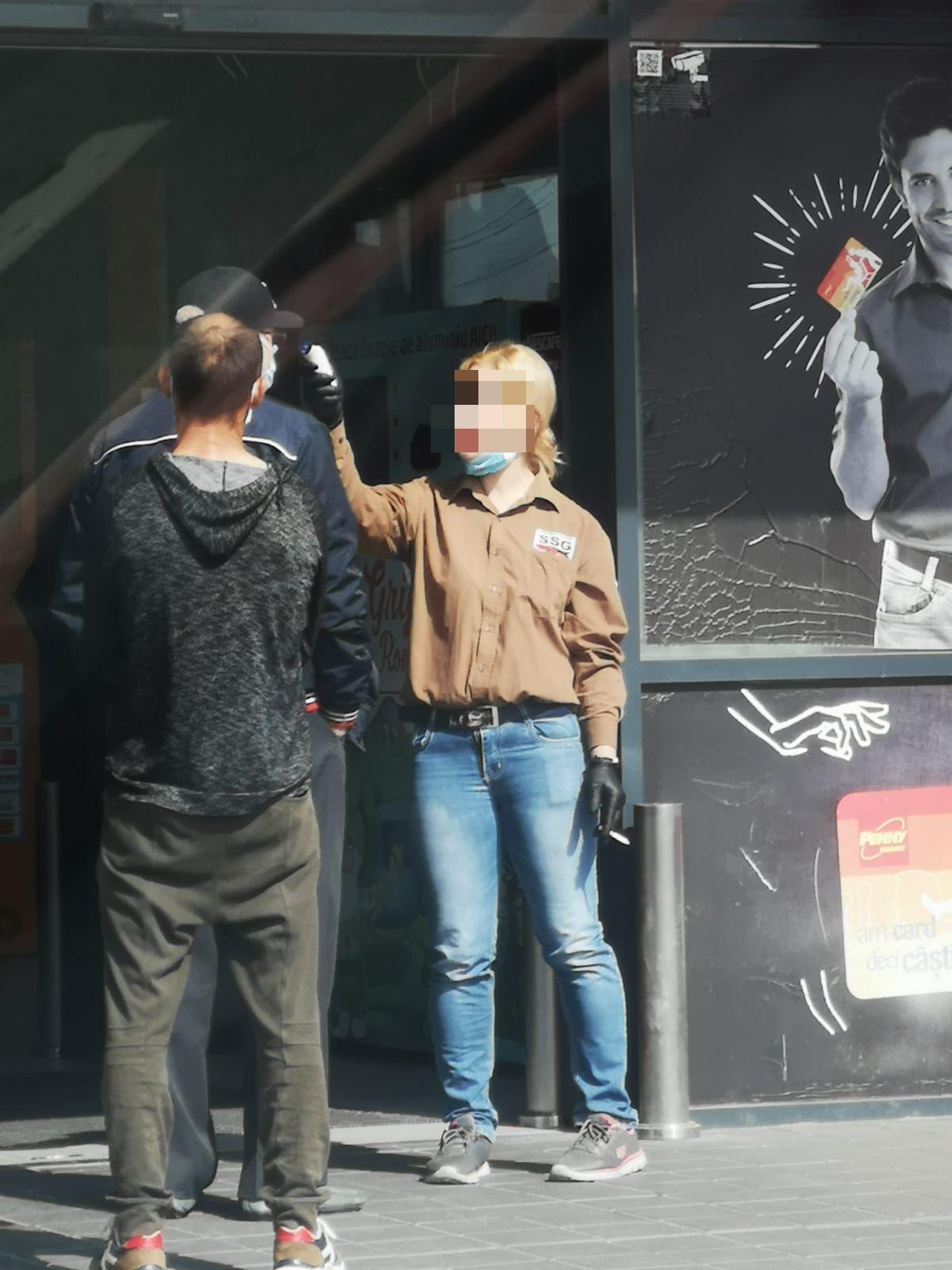 O angajată măsoară temperatura unul client Penny, în Agigea. Foto: Constanța 100%