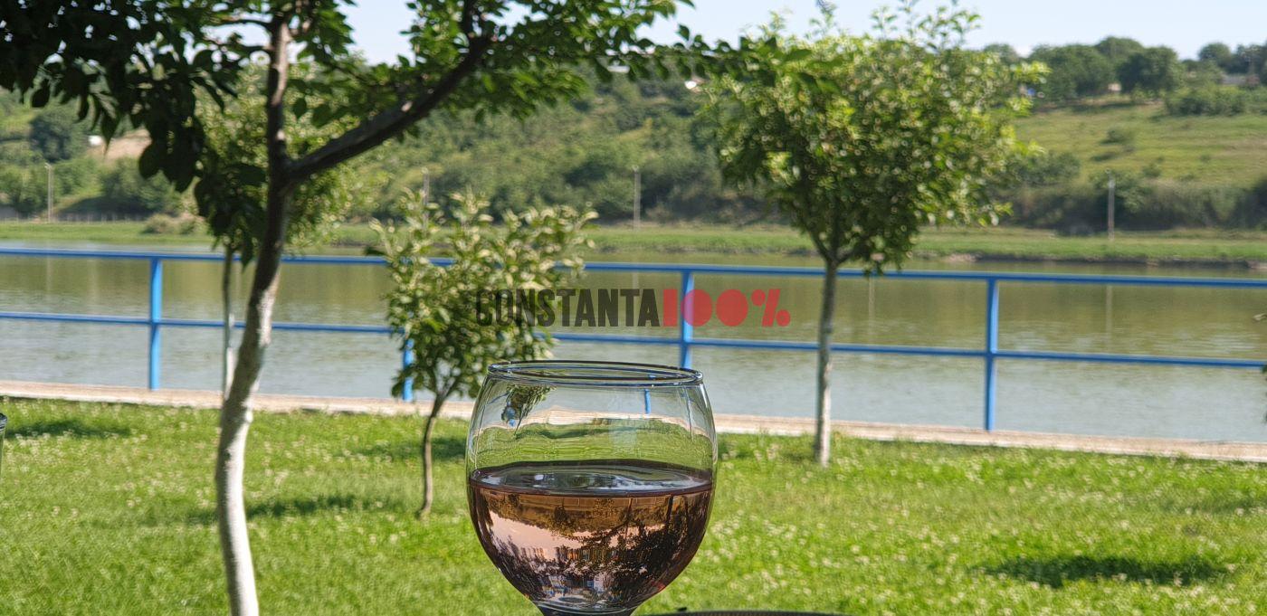 Cu un pahar de vin pe masă, pe malulul lacului Domneasca