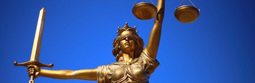 """Zeița Themis, personaj mitologic ce reprezintă justiția. Balanța și sabia pe care le poartă sunt simbolurile dreptății. Are ochii legați, pentru a simboliza că """"vede"""" cu cei interiori, care au abilitatea de a judeca faptele inculpaților pe baza unor concluzii interioare drepte, fără să fie influențată"""